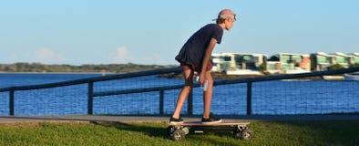 Ung man som befrias på den motoriserade skateboarden Royaltyfria Bilder