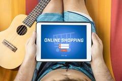 Ung man som besöker en online-shoppingwebsite med minnestavlaapparaten Royaltyfri Bild