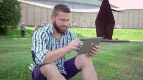 Ung man som bläddrar minnestavlan som sitter på gräs steadicam stock video
