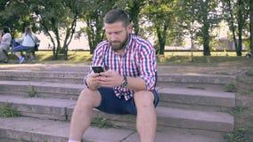 Ung man som bläddrar smartphonen Glidare- och pannaskott lager videofilmer