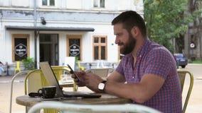 Ung man som bläddrar smartphonen i kafé lager videofilmer
