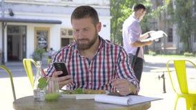 Ung man som bläddrar smartphonen, under lunch arkivfilmer