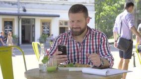 Ung man som bläddrar smartphonen, under lunch-, glidare- och pannaskott stock video