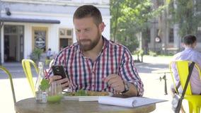 Ung man som bläddrar smartphonen, under lunch, glidareskott, rätt arkivfilmer