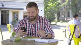 Ung man som bläddrar smartphonen, under lunch, glidareskott som lämnas lager videofilmer