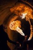 Ung man som blåser brand från hans mun Arkivbild