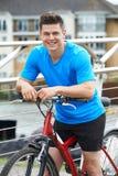 Ung man som cyklar bredvid floden i stads- inställning Royaltyfri Foto