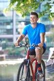 Ung man som cyklar bredvid floden i stads- inställning Royaltyfri Bild