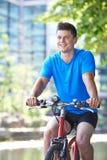 Ung man som cyklar bredvid floden i stads- inställning Fotografering för Bildbyråer