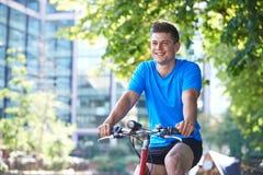 Ung man som cyklar bredvid floden i stads- inställning Arkivbild