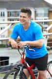 Ung man som cyklar bredvid floden i stads- inställning Royaltyfria Bilder