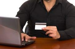 Ung man som direktanslutet köper med kreditkorten Royaltyfri Foto