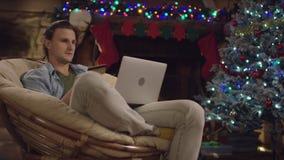 Ung man som direktanslutet shoppar, genom att använda bärbara datorn och kreditkorten i julnatt stock video