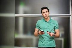 Ung man som direktanslutet shoppar på mobiltelefonen Royaltyfri Bild