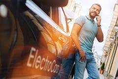 Ung man som diskuterar arbete nära elbilen Royaltyfria Bilder