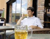 Ung man som dricker öl Arkivfoto