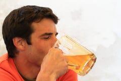 Ung man som dricker öl Arkivfoton