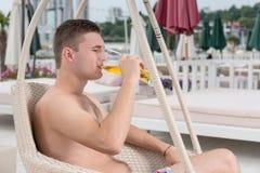Ung man som dricker ett exponeringsglas av öl på sjösidan Arkivbild