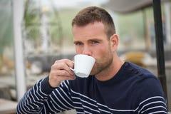 Ung man som dricker hans kaffe Arkivfoto