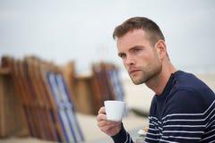 Ung man som dricker hans kaffe på stranden Arkivfoton
