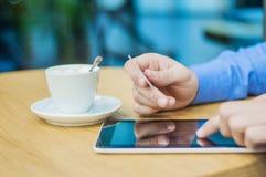 Ung man som dricker kaffe i kafé och direktanslutet shoppar arkivbild