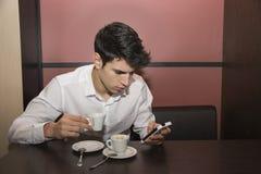 Ung man som dricker kaffe, medan se mobiltelefonen Royaltyfri Bild