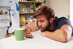 Ung man som dricker kaffe och hemma använder mobiltelefonen Royaltyfri Bild