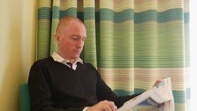 Ung man som dricker kaffe och läser en tidning i hotellrummet Lopp, folk och affärsidé lager videofilmer
