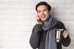 Ung man som dricker kaffe och talar på telefonen Royaltyfri Bild