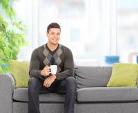 Ung man som dricker kaffe som hemma placeras på soffan Arkivbilder