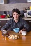 Ung man som dricker te i kök Royaltyfria Bilder