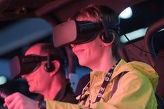 Ung man som erfar lekar med virtuell verklighetskyddsglasögon Arkivfoto