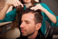 Ung man som får en frisyr Arkivfoto