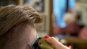 Ung man som får frisyr lager videofilmer