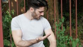 Ung man som får som stickas av den utomhus- myggan stock video