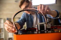 Ung man som förbinder skrivaren 3D arkivfoton