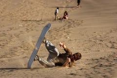 Ung man som faller, medan sandboarding på solnedgången, Huacachina, Ica, royaltyfria bilder