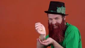Ung man som firar dagen för St Patrick ` som s isoleras på apelsinen som räknar pengar stock video