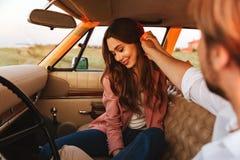 Ung man som flörtar med hans flickvän, genom att trycka på hennes hår royaltyfria bilder
