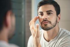 Ung man som fot applicerar anti--åldras hudomsorg för lotion Royaltyfri Fotografi
