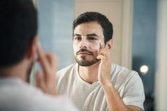 Ung man som fot applicerar anti--åldras hudomsorg för lotion Royaltyfri Foto