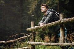 Ung man som fotvandrar i skogen Arkivfoto