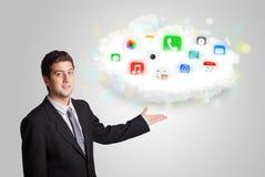 Ung man som framlägger molnet med färgrika app-symboler och symboler Royaltyfria Bilder