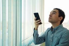 Ung man som framme använder en smartphone av ett fönster Arkivfoton