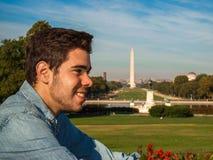 Ung man som framme poserar av Ulyssesen S Grant Memorial nationell galleria och Washington Monument i Washington DC arkivfoton