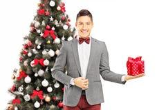 Ung man som framme står av en julgran med gåva royaltyfri foto