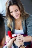 Ung man som föreslår romantiskt till flickvännen Fotografering för Bildbyråer