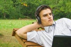 Ung man som fungerar på bärbar dator i parken Royaltyfria Foton