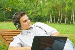 Ung man som fungerar på bärbar dator i parken Fotografering för Bildbyråer