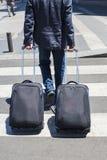 Ung man som går med två resväskor Arkivbild